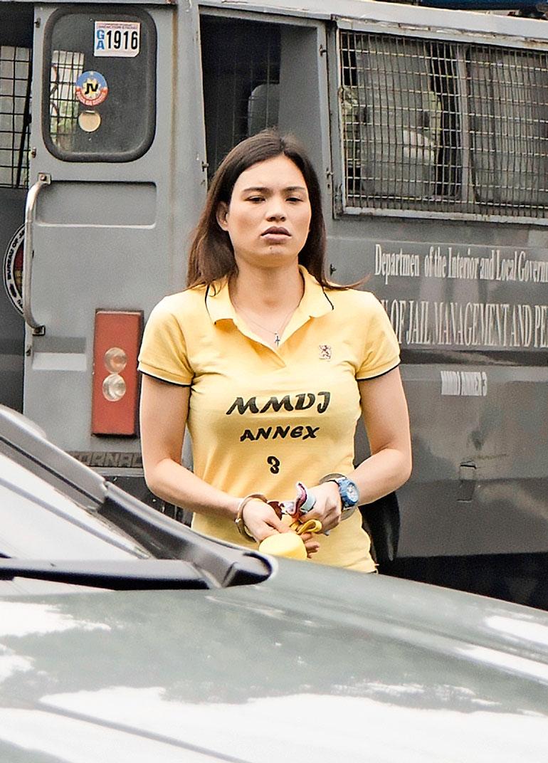 Maria Mustonen tuotiin vankilasta oikeustalolle käsiraudoissa. Hänellä oli kaulassaan ristiriipus ja kädessään kello.
