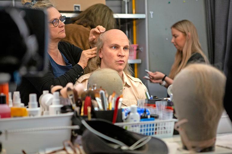 Maskeeraaja Riikka Virtanen viimeistelee Rikun Juice-tyylin. – Onneksi saa peruukin, ettei ole tarvinnut hiuksia kasvattaa, kiloja vyötärölleen rohmunnut näyttelijä virnistää.