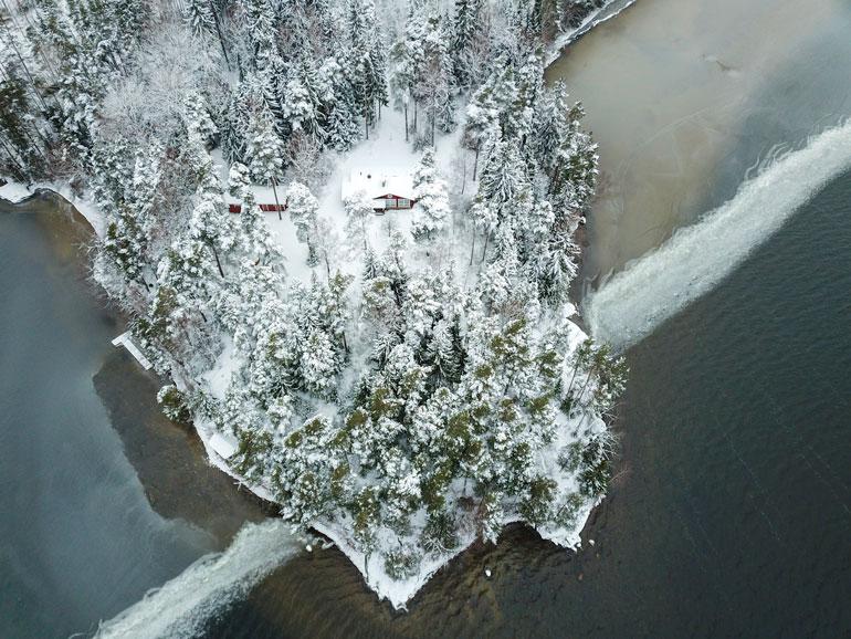 Mökki sijaitsee idyllisen järven rannalla niemen kärjessä.