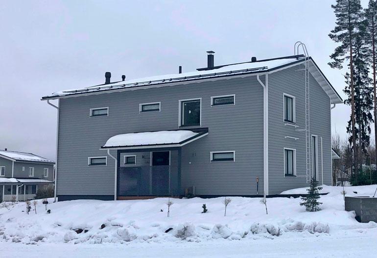Harmaa pytinki on valmistunut vuonna 2013. Kaksikerroksinen talo sointuu hyvin perheen autojen väreihin.