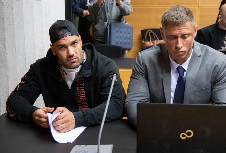Mustaan huppariin ja lippikseen sonnustautunut Mike Soldier sekä asianajaja Helsingin käräjäoikeudessa viime viikon keskiviikkona.