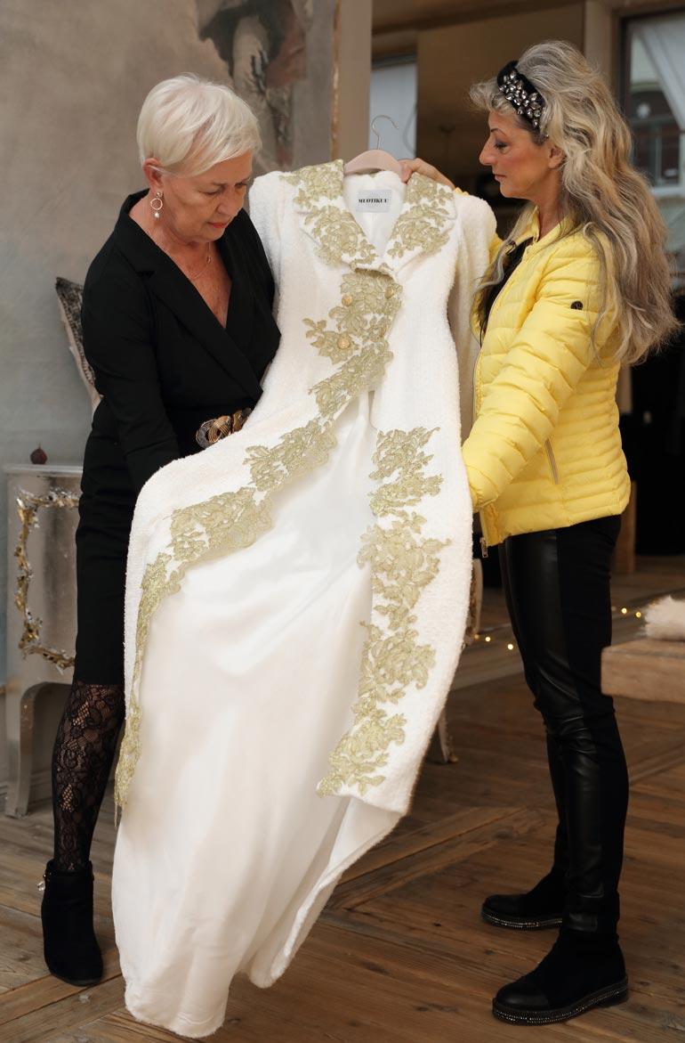Muotikuun Jaana Varkki-Terho esittelee valmista pukua Kikelle.
