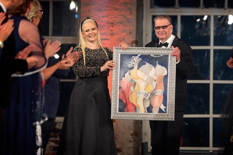 Missikeisarin viitan perinyt Sunneva Kantola ojensi Einolle Miss Suomi 2019 -finaalissa Johanna Oraksen maalaamaan Kruunajaiset-taulun.