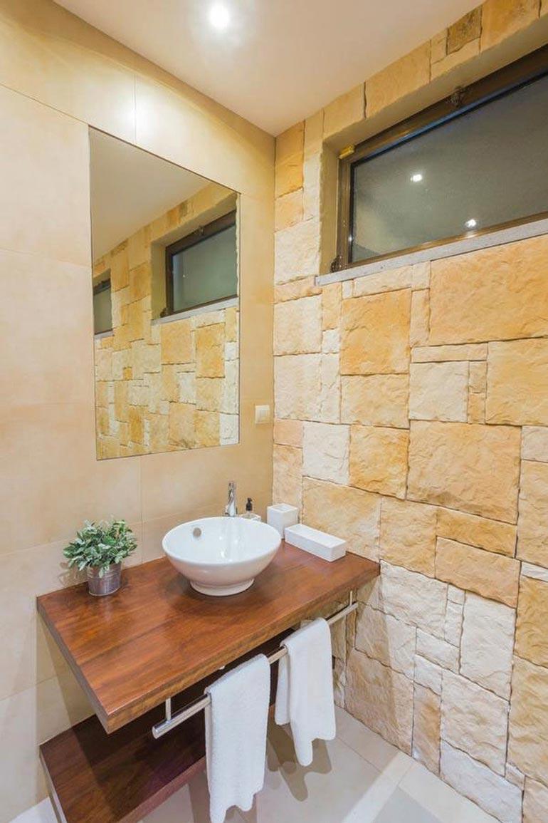 Jokaisen makuuhuoneen yhteydessä on oma kylpyhuone. Maanläheinen tyyli näkyy niissäkin.