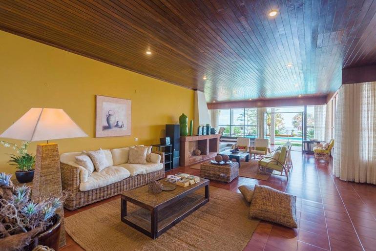 Rottinkisin huonekaluin sisustetusta olohuoneesta avautuvat kauniit näkymät pihalle ja uima-altaalle.