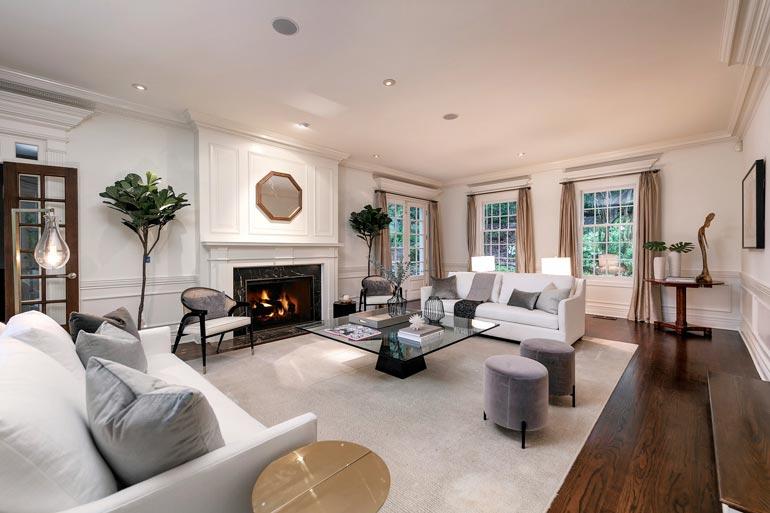 Suuri olohuone on sisustettu maanläheisin sävyin. Olohuoneen tunnelman täydentää takka.