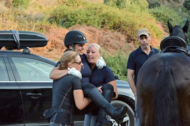 Minna Ala-Varvi ja Tiia Dahlqvist auttavat Jaanan muun muassa hevosen selkään ja sieltä alas. Valmentaja Antonio Serrano Silva seuraa tarkkana.