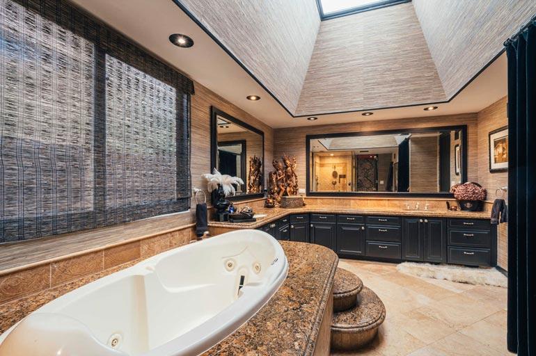 Valtava kattoikkuna loistaa luonnonvaloa kylpyammeeseen. Kivipintaiset tasot tuovat ylellisyyden tuntua.