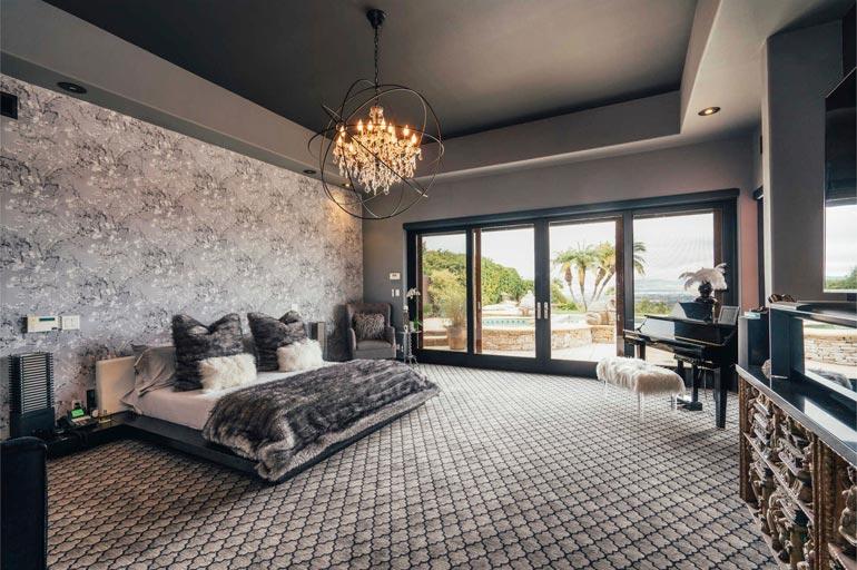 Hopean sävyisenä hohtavan makuuhuoneen nurkassa on yksi talon lukuisista pianoista.
