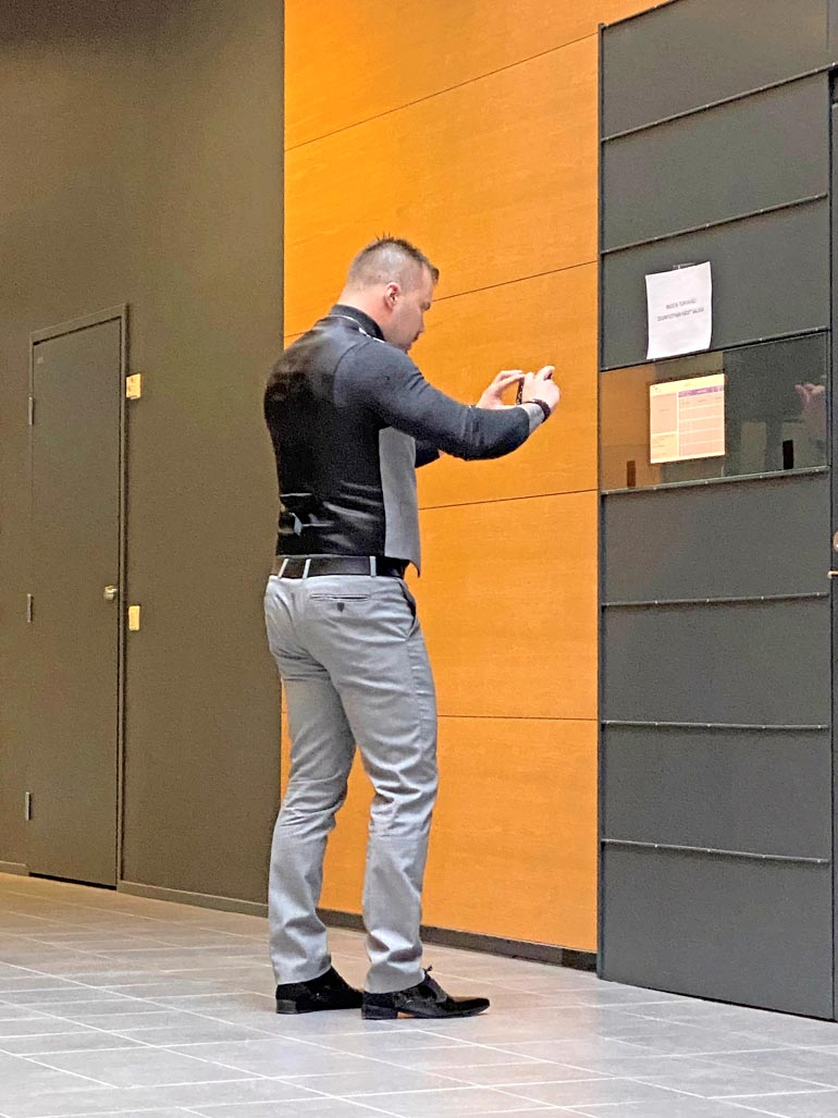 Koskelo napsi useita kuvia oven vieressä olevasta syytetaulusta ennen käräjäsaliin pääsyä.