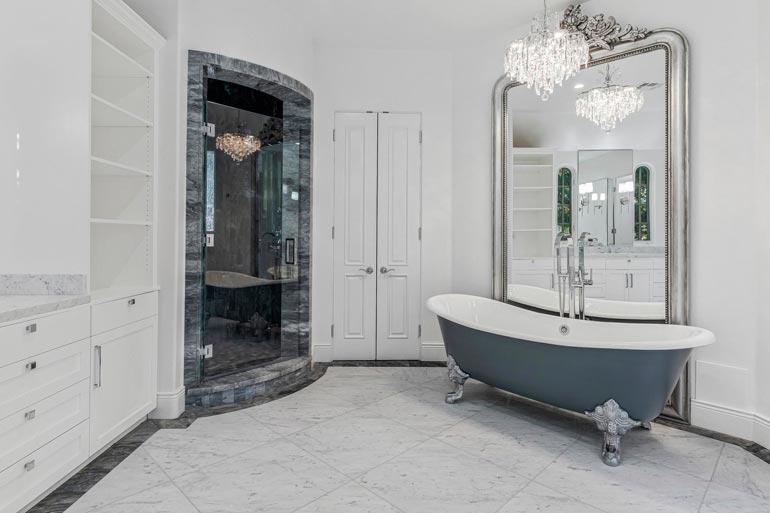 Pääkylpyhuone jatkaa sisustuksen vaaleaa linjaa. Ylellisyyttä tilaan tuovat kattokruunu ja valtava koristeellinen peili.