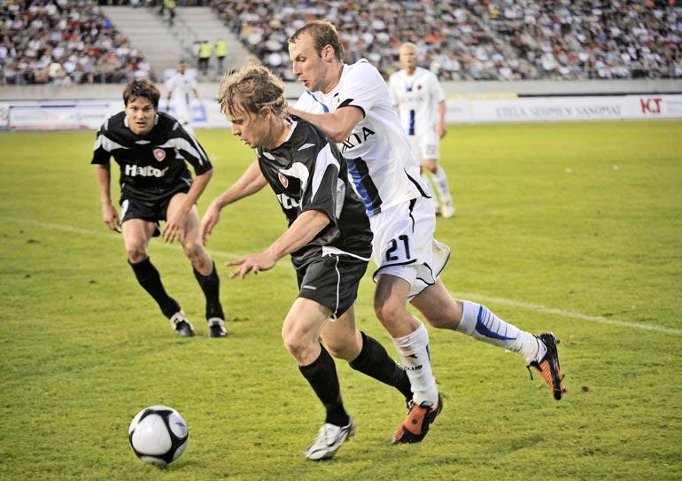 Vuonna 2009 Konsta (musta paita) pelasi jalkapallon Eurooppa-liigan karsinta- ottelussa belgialaista Bruggea vastaan. Taustalla tilannetta tarkkailee Jari Litmanen.