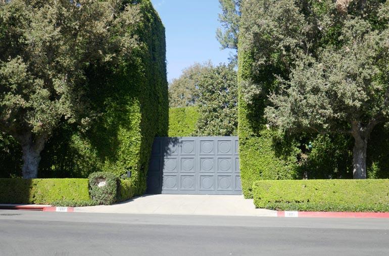 Kadulta ei  pihaan näe,  sillä paksu  portti pitää  tunkeilijat  loitolla.  Tiheän  pensasaidan  läpikään tuskin pääsee  tirkistelemään.