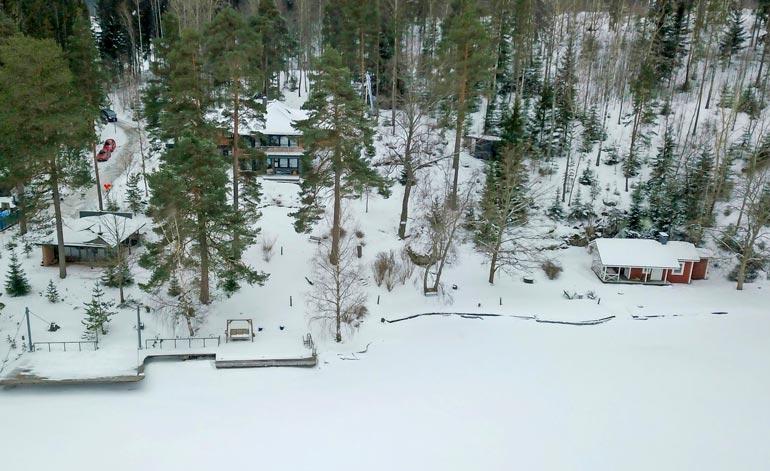 Tilusten koko  ja rakennusten  näyttävyys  paljastuvat  lumipeitteen altakin.  Massiivisen  laiturin takana  on rantasauna, oikealla  puolestaan kesäkeittiö.
