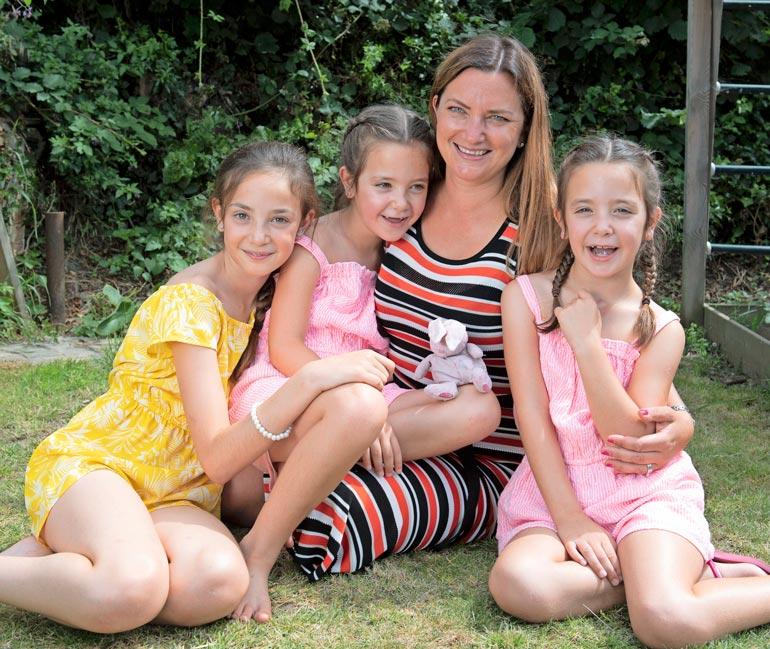 Angela-äiti kiittää kädet ristissä siitä, että hänellä on terveet tyttäret. Kuvassa myös perheen esikoinen.