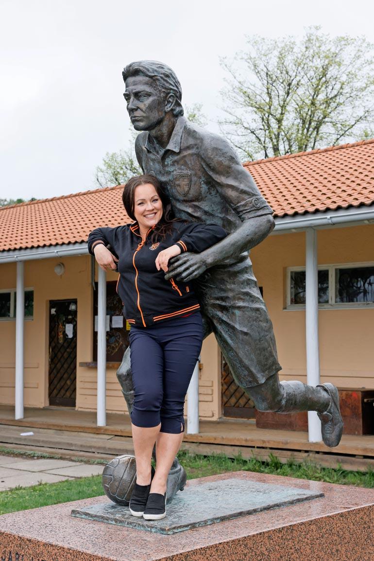 Oi Lahti on! Reippaan mimmiksi tunnustautuva Heidi lepää kuninkaan patsaan käsivarsilla.