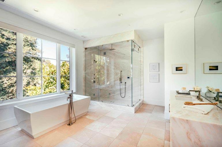 Valkoiseen kylpyhuoneeseen tulvii valoa suuresta ruudukkoikkunasta.