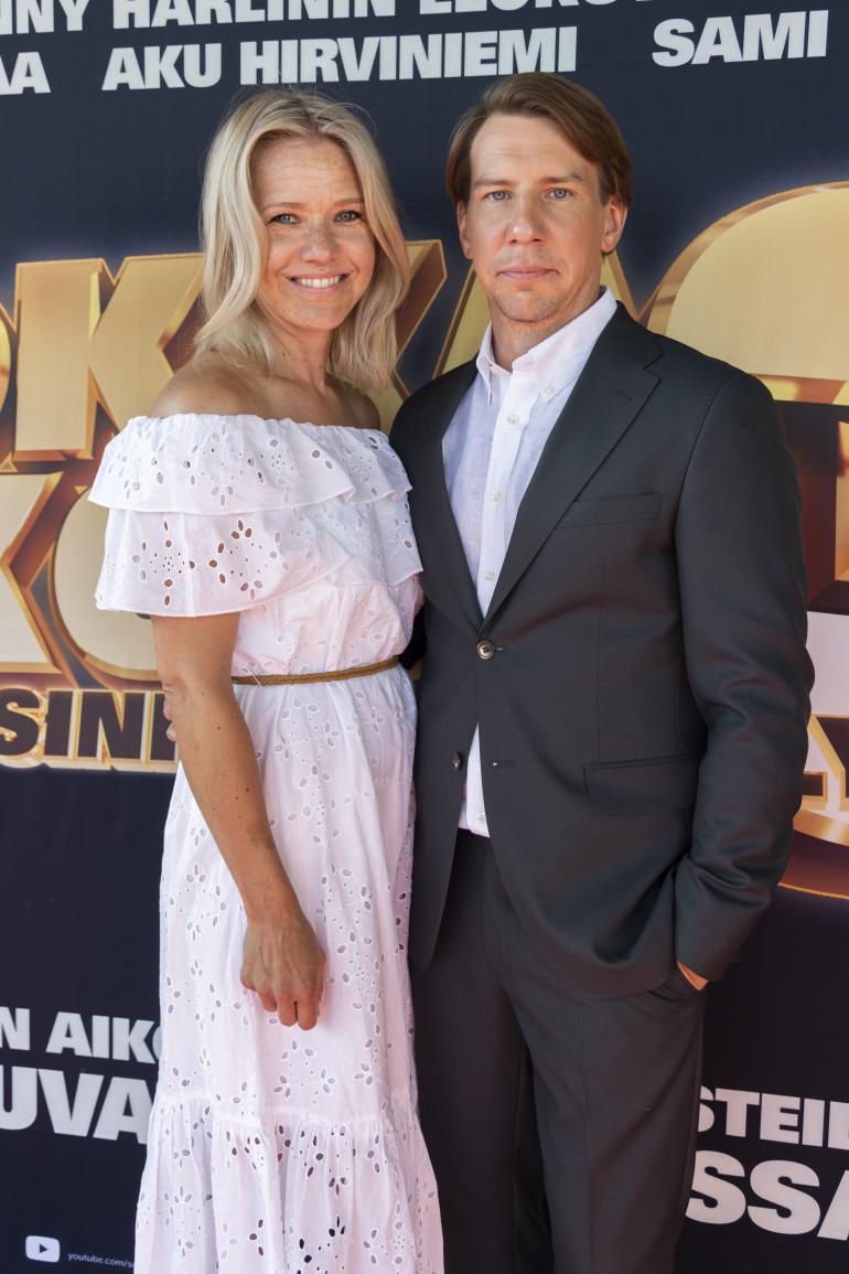 Akun toimittajapuoliso Sonja Kailassaari oli pukeutunut ensi-iltaan kevyen kesäisesti. Olkapäät paljastava, valkoinen mekko korosti kauniisti Sonjan rusketusta.