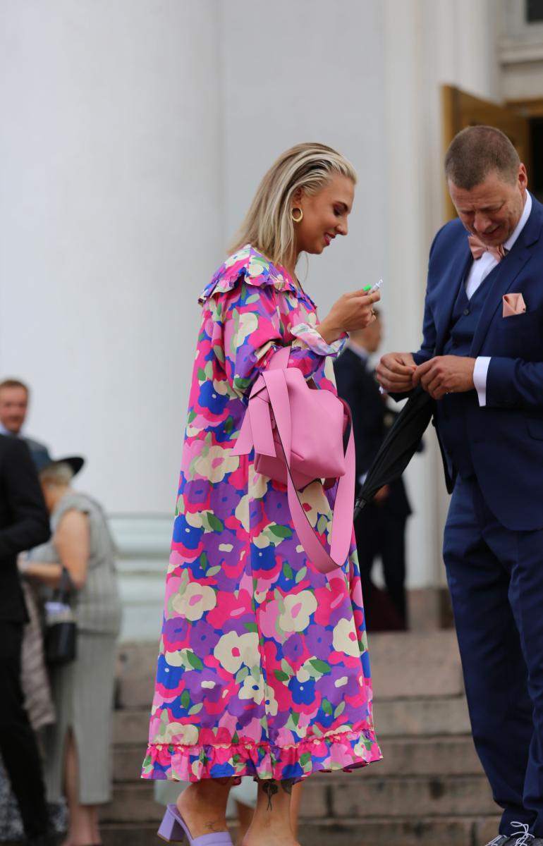 Veronica Verho häikäisi sateisesta säästä huolimatta. Hän oli valinnut ylleen näyttävän kukkamekon ja sen seuraksi kirkkaan pinkin käsilaukun.