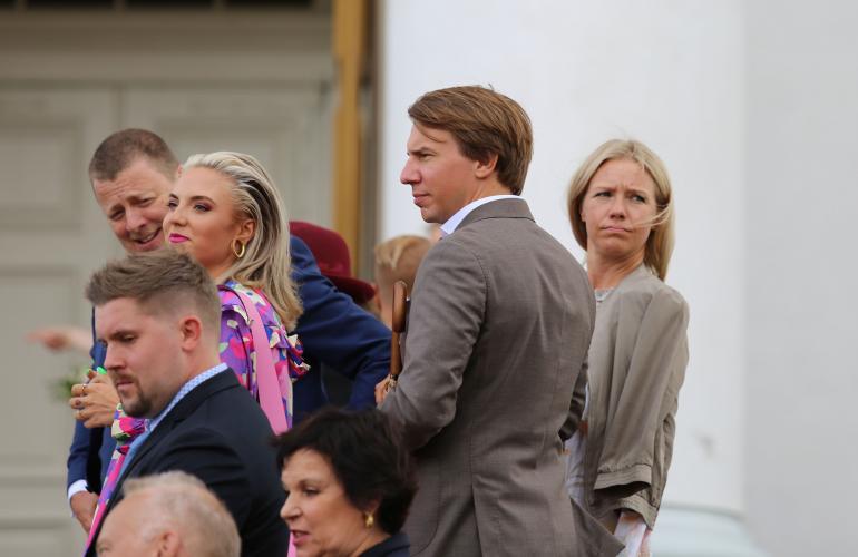 Toimittaja Sonja Kailassaari kurkki puolisonsa Aku Hirviniemen takaa tuiman oloisena.