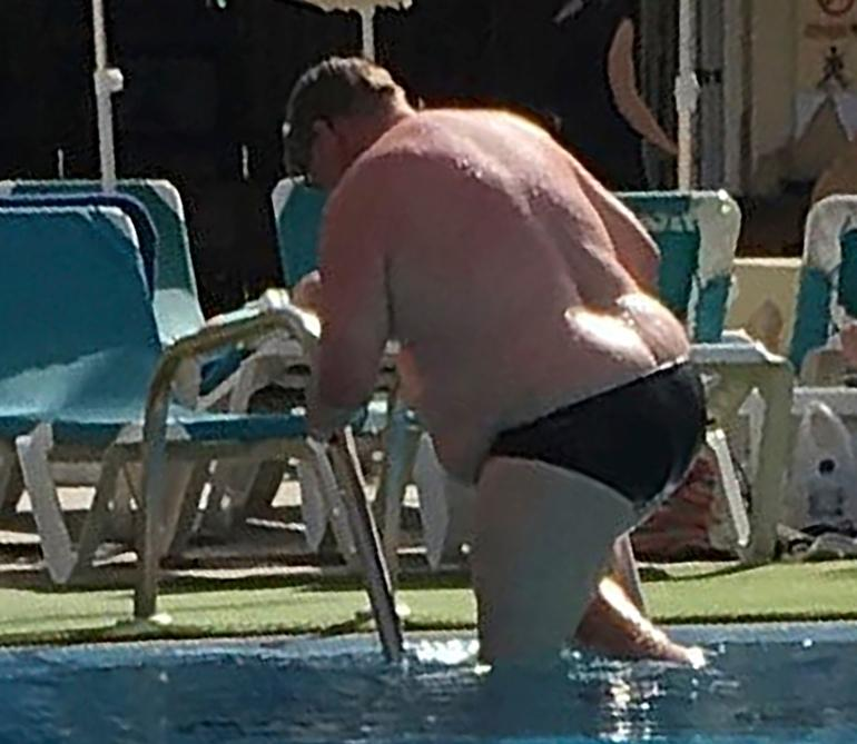 Timo Soini uimahousuissa nousemassa altaasta.