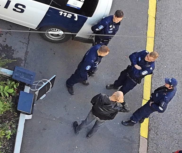 Riku poliisien ympäröimänä.