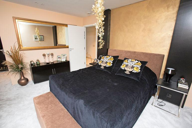 Jennin makuuhuoneen seinää koristaa kultareunustettu peili.