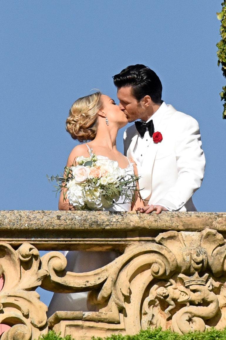 Tuore hääpari jakoi intohimoisen suudelman huvilan parvekkeella.