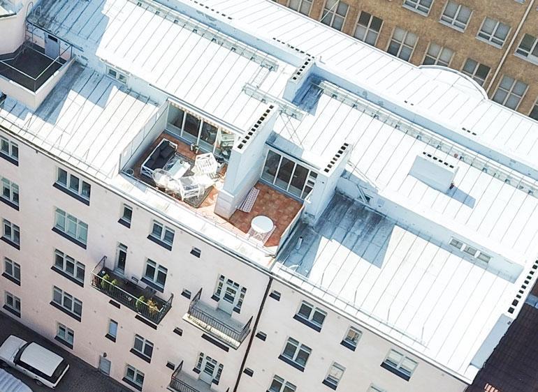 Ylimmän kerroksen huoneiston kruunaa kattoterassi, joka avautuu sisäpihan suuntaan.