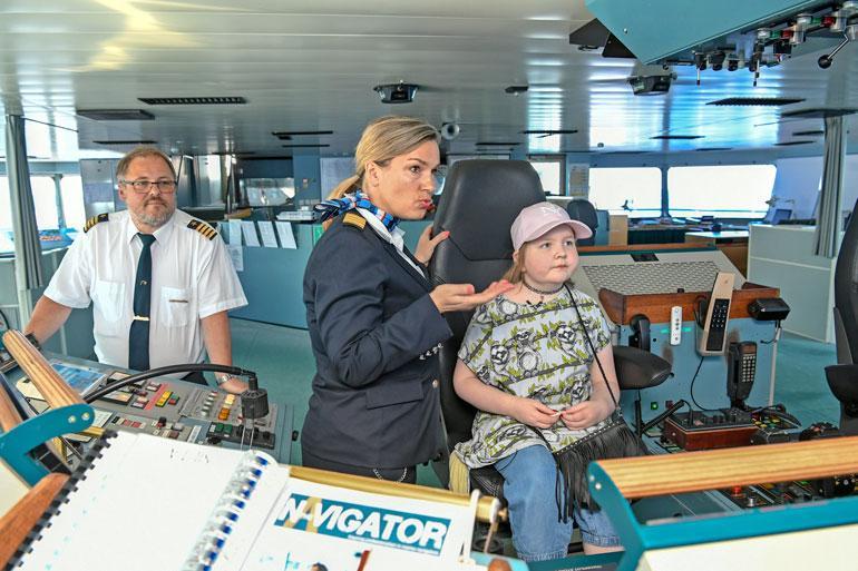 Silja Serenaden intendentti Taru Backmann kertoo Iirikselle laivasta komentosillalla. Kapteeni Juha Rantavirta seuraa taustalla, kun jännittynyt pikku-Iiris pääsee istumaan oikein kapteenin tuolille.