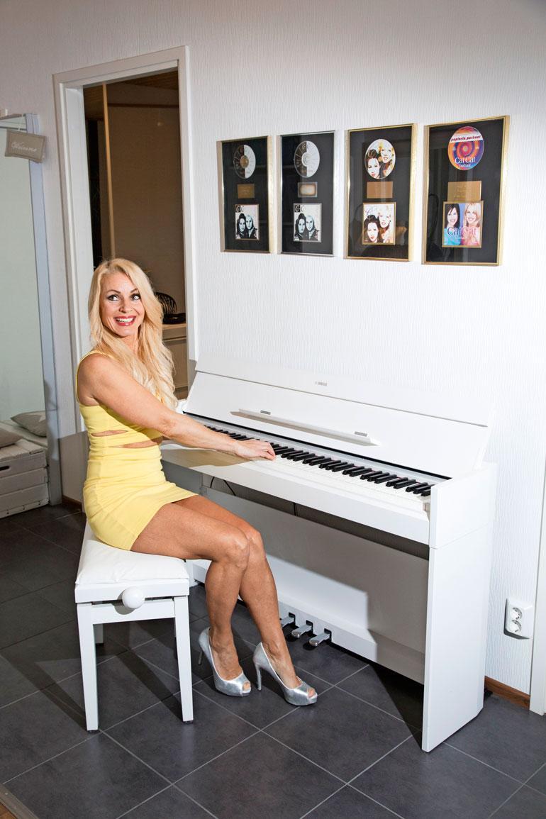 Virpin kotiin on pianon yläpuolelle ripustettu CatCat-yhtyeen kulta- ja platinalevyt.
