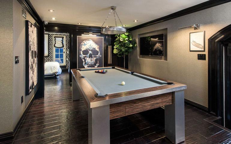 Biljardihuoneeseen on luotu moderni ilme pääkallotaiteella viileän sinertävällä biljardipöydän veralla.