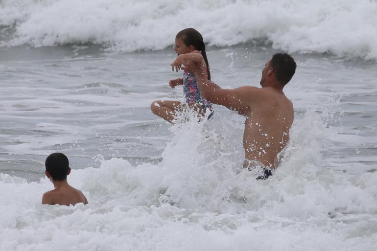 Tom leikki omien ja vieraiden lasten kanssa ja heitteli heitä aaltoihin.