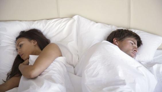 Tyytymätön pari sängyssä.
