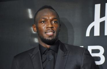 Usain Bolt biletti nuorten naisten kanssa.
