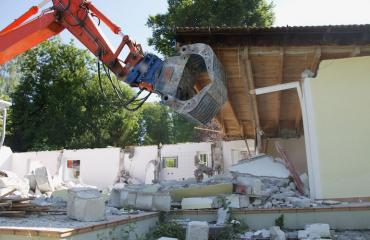 Mies tuhosi rakentamiaan taloja.