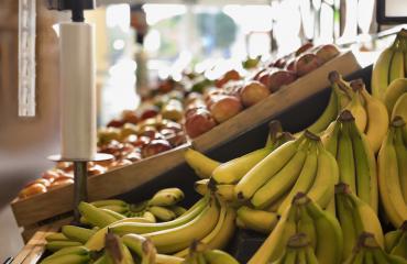 Mies hieroi kaupan hedelmiä takamukseensa.